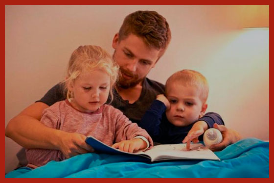 многодетный отец читает книжку детям